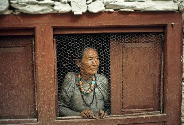 Женщина у окна в непальской деревне