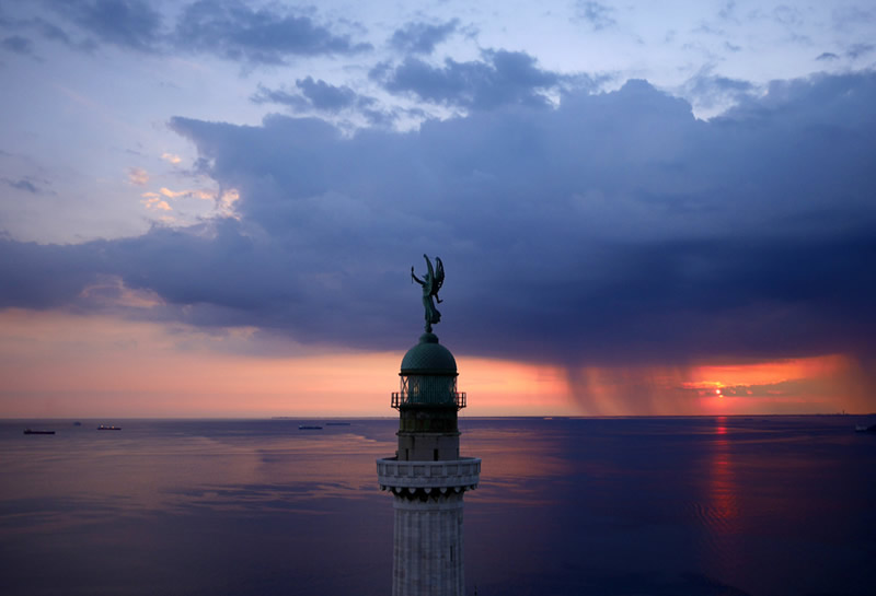 Маяк Фаро делла Виттория (маяк Победы) на закате с видом на залив в городе Триест