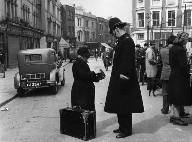 Полицейский помогает даме на Портобелло-Роуд в Лондоне, 1951. Автор Курт Хаттон