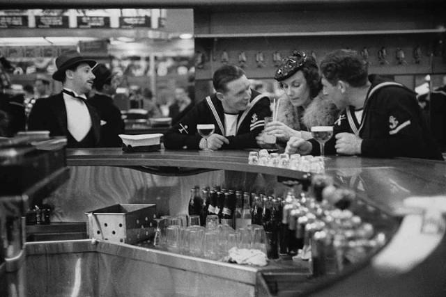 «Привет, милая». Британские моряки общаются с женщиной в нью-йоркском баре, 1939. Автор Курт Хаттон
