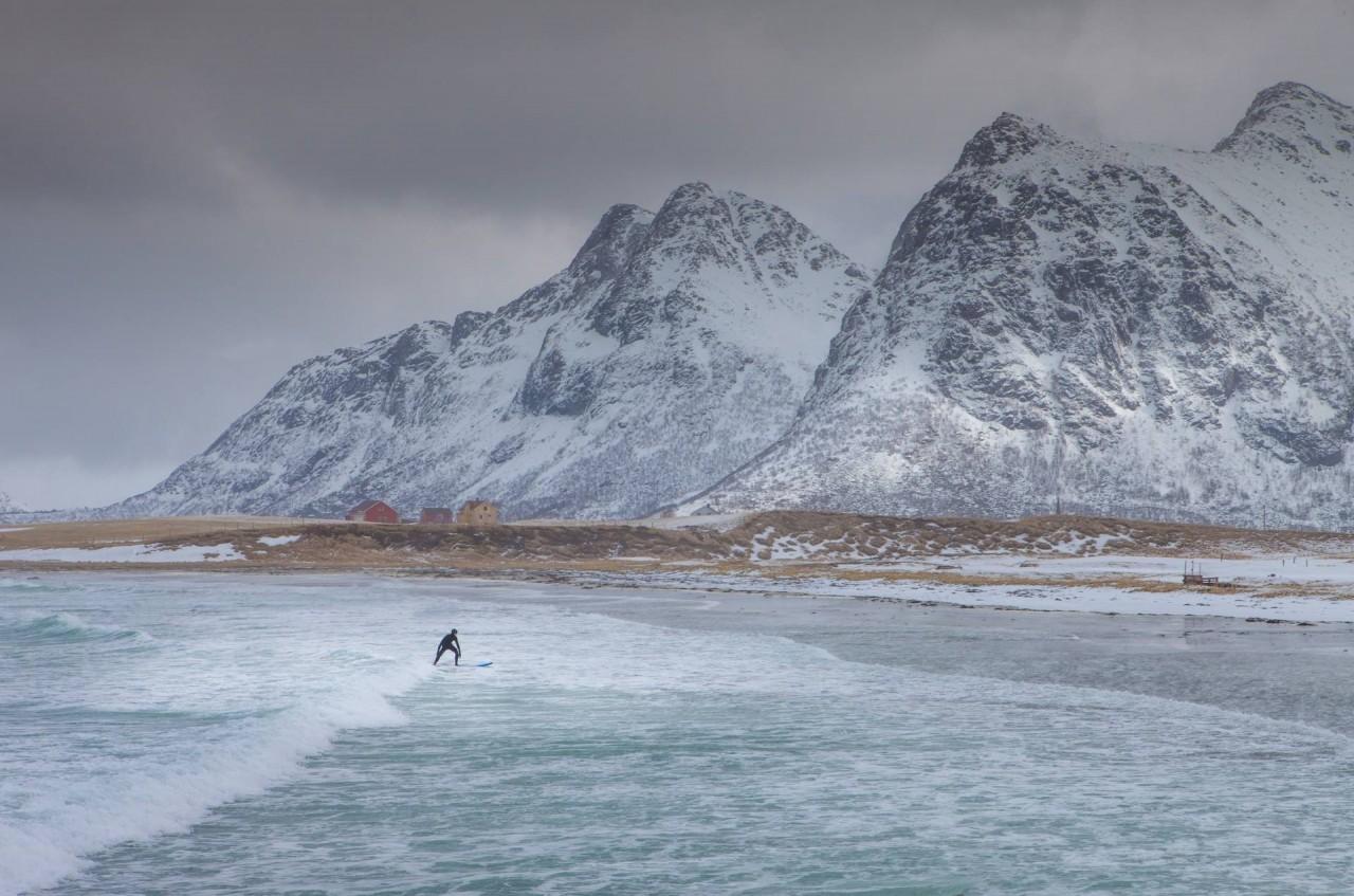 Сёрфер в океанских водах Северной Норвегии после снегопада. Автор Петер Свобода