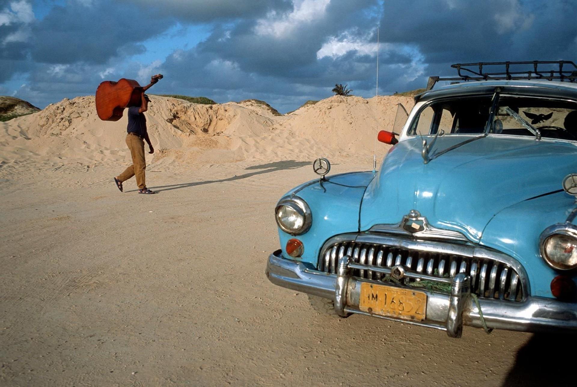 По пляжу бродит музыкант. Санта-Мария-дель-Мар, Гавана, Куба, 1998. @ Дэвид Алан Харви
