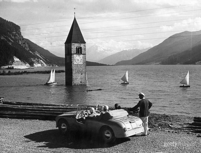 Искусственное озеро Решен в Южном Тироле, созданное в 1950 году, когда строили плотину. Над водой возвышается колокольня старой церкви, стоявшей в затопленной деревне Граун. Италия, 1953