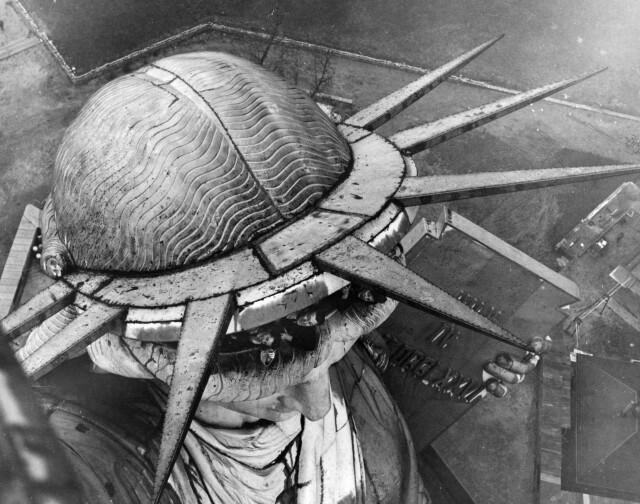 Туристы выглядывают из короны Статуи Свободы, снято со смотровой площадки на факеле, примерно в 1930 году