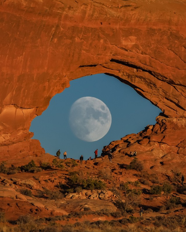 Луна, похожая на гигантский глаз, смотрящий через скальную арку в пустыне. Национальный парк Арчес, Юта. Фотограф Зак Кули