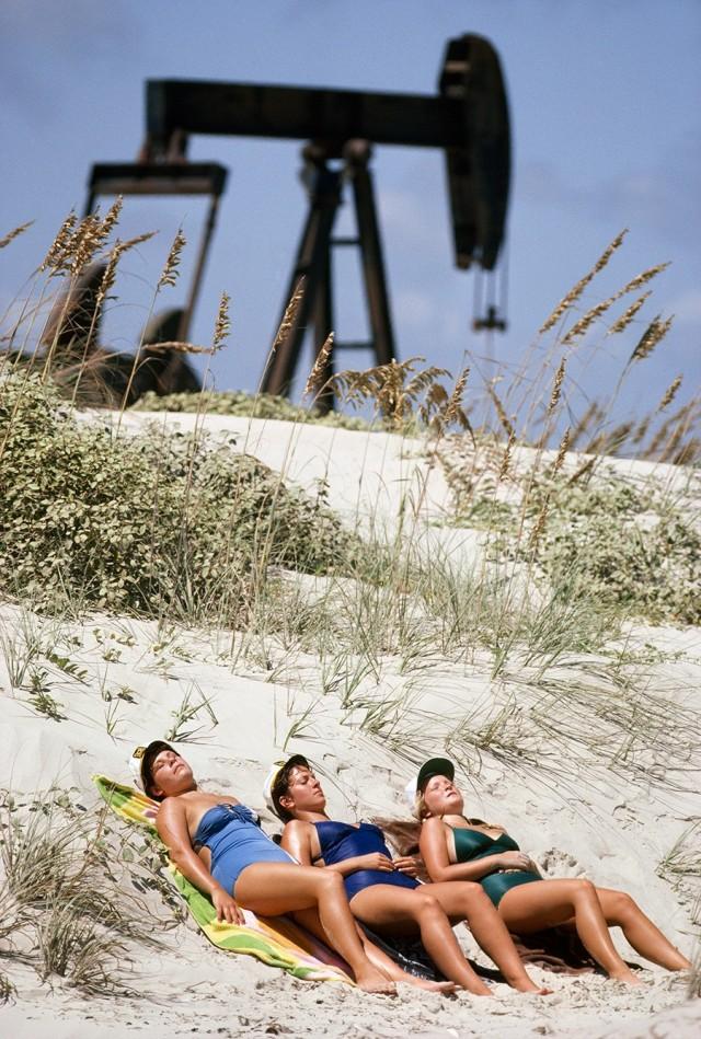Загорающие женщины и нефтяные насосы, остров Падре, Техас, 1980. Фотограф Гордон Гаан