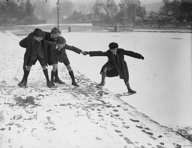 Школьники «пробуют» лёд на озере в Хэмпстеде, Англия, 1924. Архив Getty Images