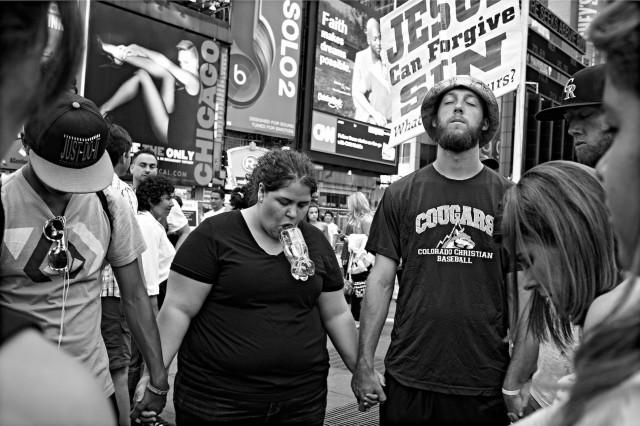 Туристы молятся на площади Таймс-сквер, Нью-Йорк. Фотограф Бетси Карел