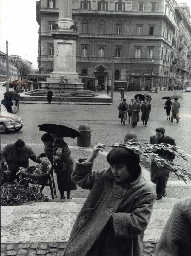Девушка купила зеленую веточку, и, поскольку начинается дождь, она покрывает ею голову, Рим, Италия, 1958. Фотограф Леонард Фрид