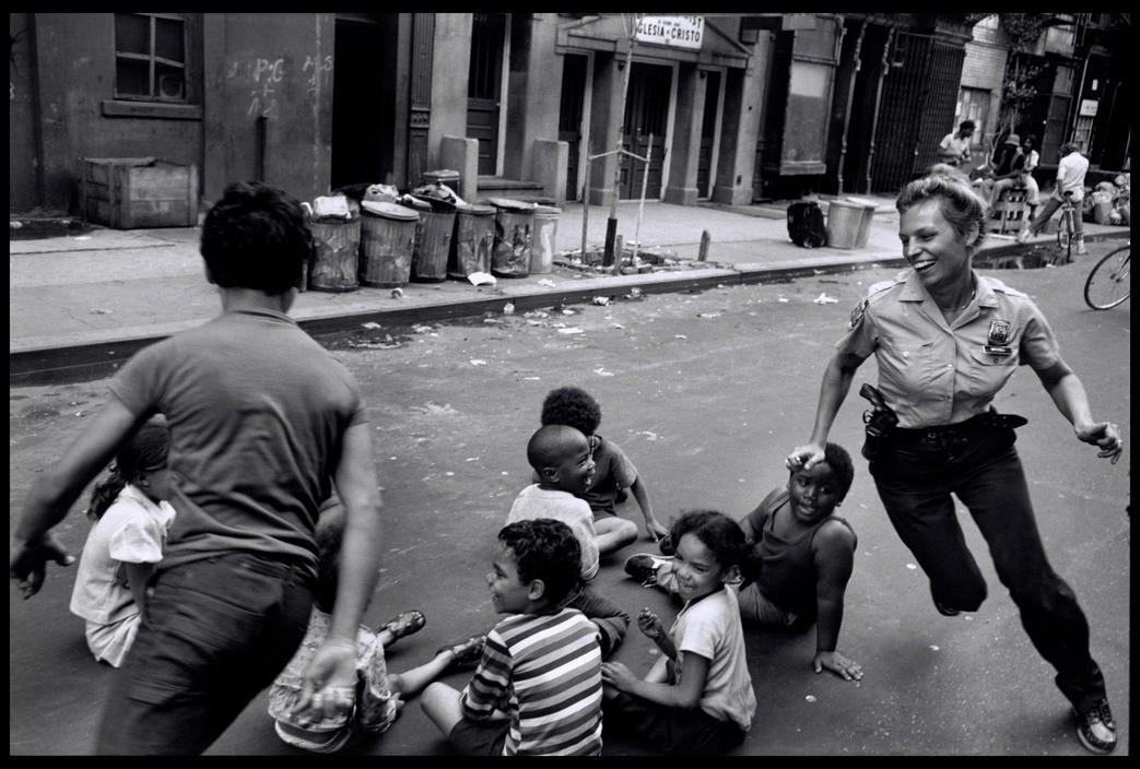Женщина-полицейский играет с местными детьми в Гарлеме, Нью-Йорк, США. 1978. Фотограф Леонард Фрид