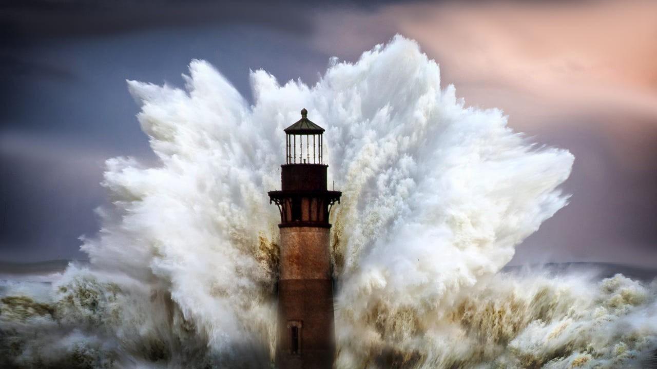 Огромная волна обрушивается на маяк. Фотограф Грег Уотерс