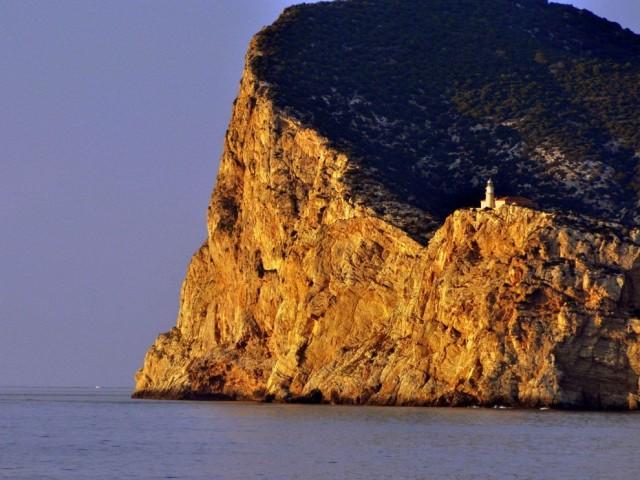 Солнце освещает морскую скалу и маяк в Испании. Фотограф Люси Уайт