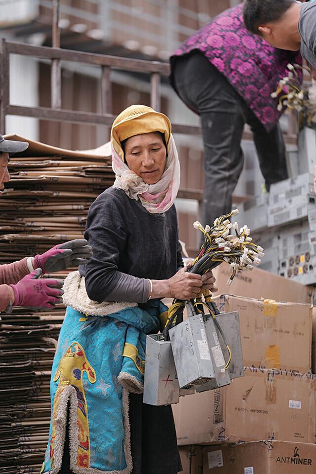 Тибетская женщина с блоками питания для майнинга криптовалют. Фотограф Ding Gang