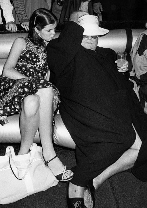 Трумен Капоте уснул в «Студия 54». На тапках видны инициалы писателя. Фотограф Рон Галелла