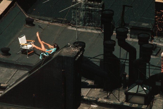 Девушка загорает на крыше Манхэттена, Нью-Йорк, 1983 год. Фотограф Томас Хёпкер