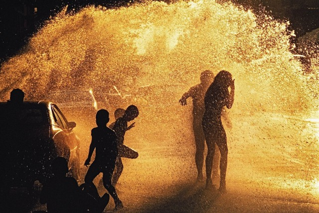 Дети играют в брызгах воды из гидранта на одной из улиц Гарлема, Нью-Йорк, 2013 год. Фотограф Томас Хёпкер