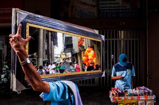 2 место в категории «Уличная фотография», 2020. Мужчина с зеркалом на улице в Медельине, Колумбия. Автор Майкл Ковальчик