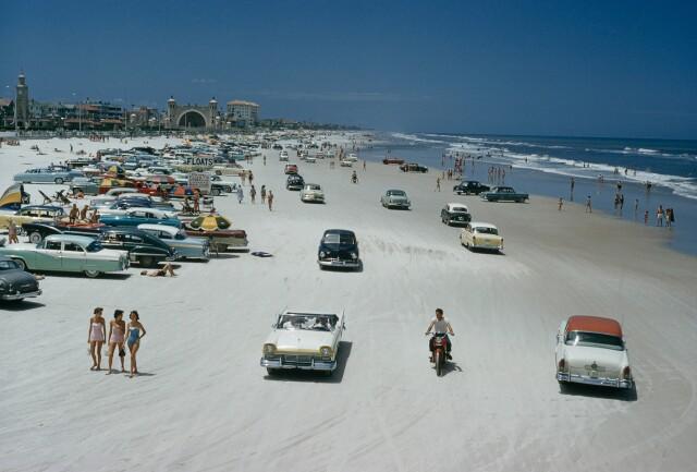 Автомобили, мотоциклы и любители позагорать на пляже в Дейтона-Бич, штат Флорида. Фотограф Дж. Бейлор Робертс
