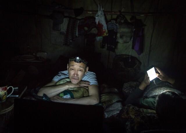 Охотник Григорий Замятин смотрит фильм на своём ноутбуке в палатке перед сном, Саха. Фотограф Алексей Васильев