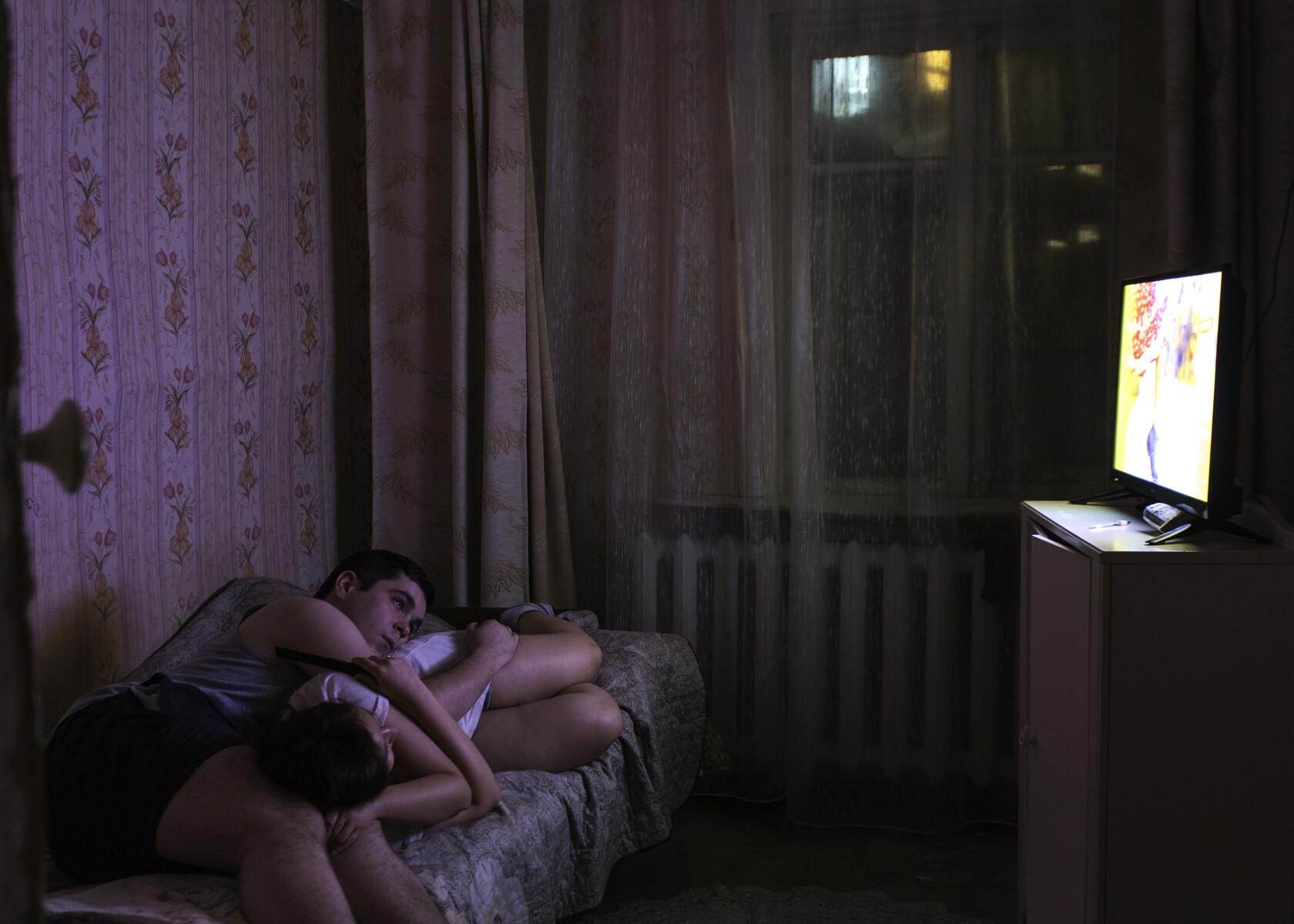 Молодая пара Иван и Инна смотрят телевизор дома в Якутии. Фотограф Алексей Васильев