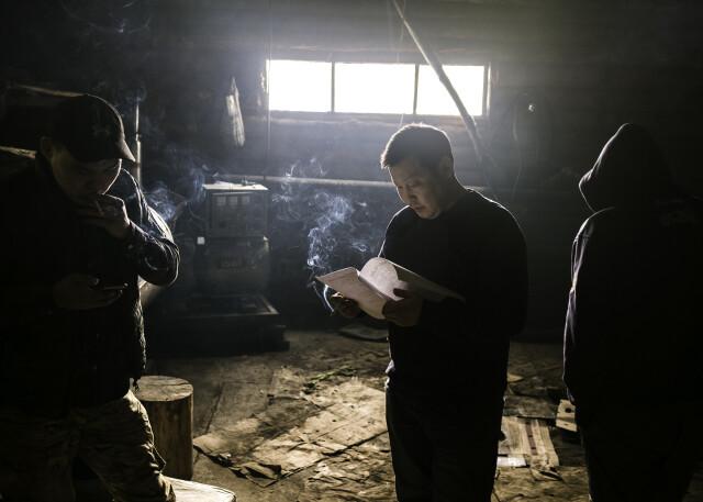 Актёры, играющие роли дальнобойщиков в драме «Чёрный снег», репетируют в курилке придорожного кафе, где проходит съёмка. Фотограф Алексей Васильев
