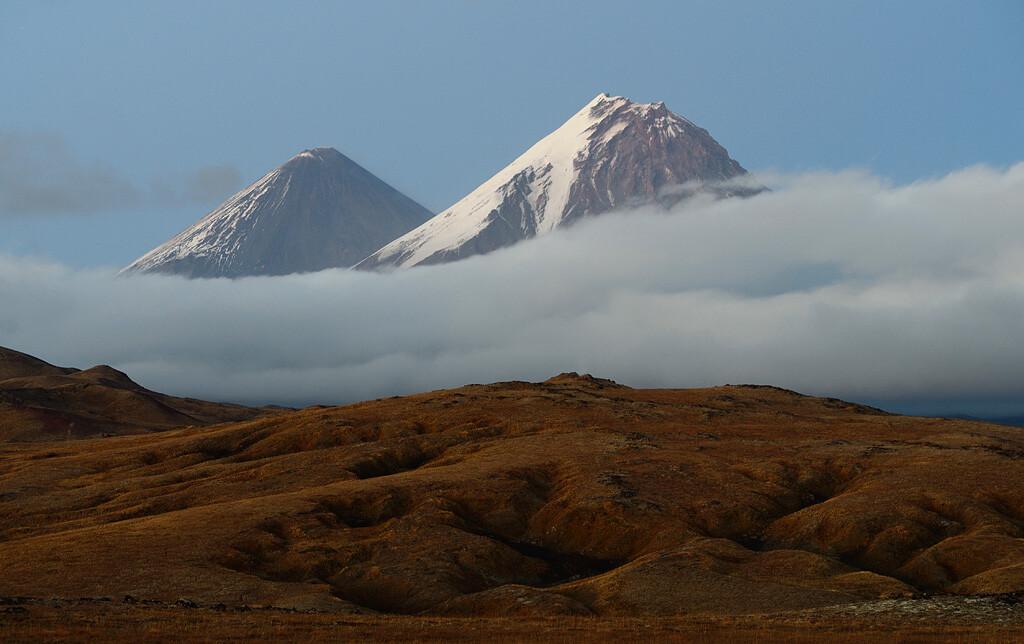 Природный парк «Ключевской». Осеннее вулканическое плато на высоте около полутора километров. Над ним возвышаются вулканы Ключевской и Камень. Фотограф Игорь Шпиленок