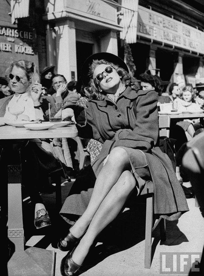 Люди греются в лучах солнца, сидя в кафе на тротуаре. Берлин, Германия, 1946. Уолтер Сандерс