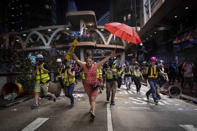 Женщина с зонтиком (символ протеста) во время демонстраций в Гонконге против законопроекта об экстрадиции, 1 октября 2019. Автор Николас Асфури