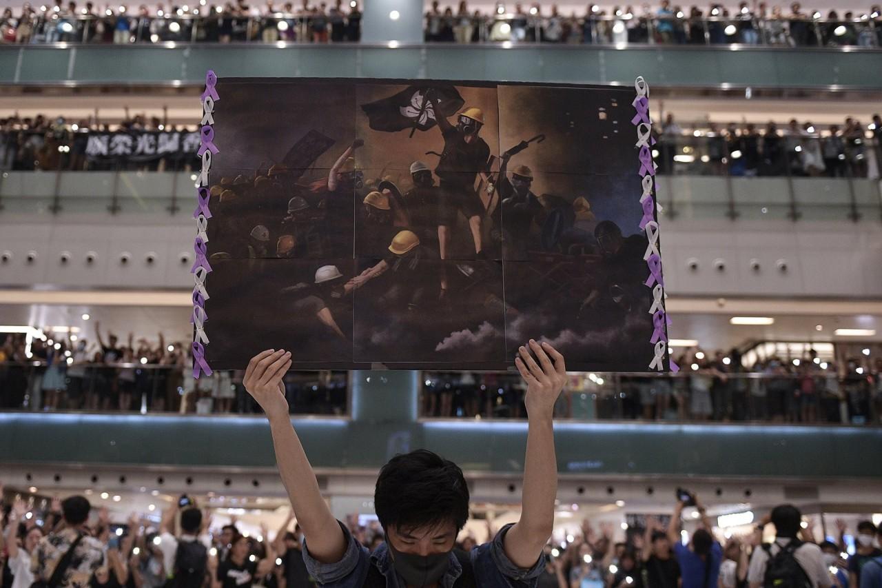 1 место в категории «Общие новости», 2020. Мужчина с плакатом среди людей, собравшихся спеть «Слава Гонконгу», негласный гимн демонстрантов в Гонконге, сентябрь 2019. Автор Николас Асфури