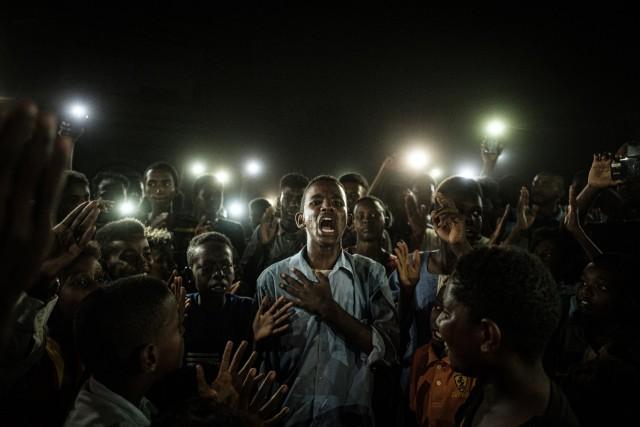 «Фото года», 2020. Участник протестов против режима Омара аль-Башира читает стихи в свете телефонов при отключенной электроэнергии в Хартуме, Судан. Автор Ясуёси Тиба