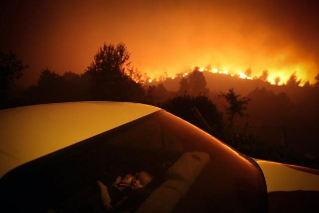 3 место в категории «Главные новости», 2021. Ребёнок в машине на фоне лесного пожара в Оливейра-де-Фрадеш, Португалия. Автор Нуно Андре Феррейра