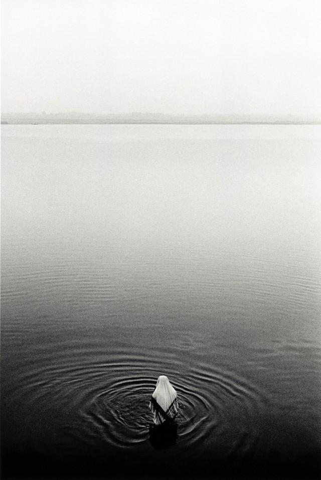Женщина, молящаяся на рассвете в реке Ганг. Варанаси, Индия, 2005. Автор Уолтер Ротуэлл
