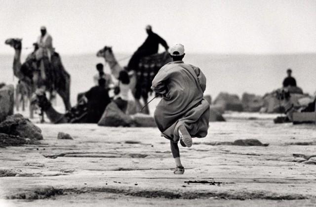 Молодой человек бежит за своим отцом на верблюде. Пирамиды Гизы, Египет. Автор Уолтер Ротуэлл