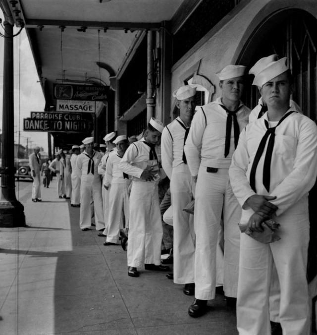 Моряки стоят в очереди за местами в пивной. Автор Уэйн Миллер