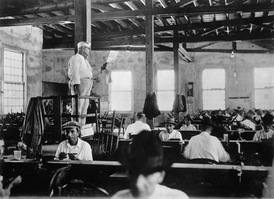 A lector reads a newspaper to workers in a Key West Florida cigar factory