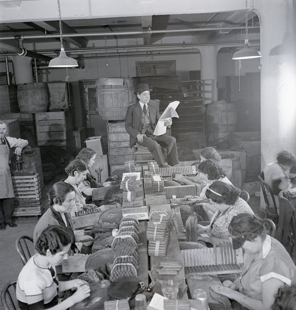 A lector reads a newspaper to workers in a cigar factory