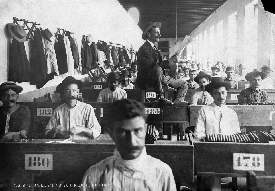 A lector reads to workers in a Cuban cigar factory